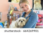 Stock photo portrait of young woman and her dog in pet store 664269901