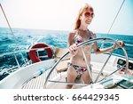 young woman in bikini steering... | Shutterstock . vector #664429345