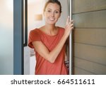 young woman opening house front ... | Shutterstock . vector #664511611