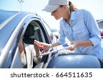 woman in parking lot renting... | Shutterstock . vector #664511635