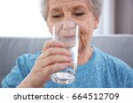 elderly woman drinking water at ... | Shutterstock . vector #664512709