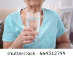 elderly woman holding glass of