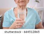 elderly woman holding glass of