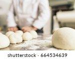 baker kneading dough in a... | Shutterstock . vector #664534639