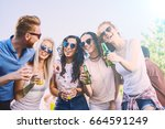 friends at festival  drinking ... | Shutterstock . vector #664591249
