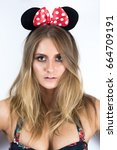 Small photo of Beauty portrait of a young girl with beautiful blonde hair Mickey mouse ears on her head