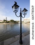 Street Lantern or Lamp in Singapore City along the River, with Pigeons sitting on it and the City Skyline in the background! - stock photo