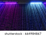 curtain of falling water with colorful led light on dark background, selective focus
