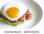 Small photo of egg sunny side up on a bed of guacamole egg sunny side up on tomato tartar with avocado