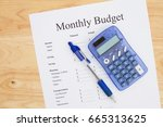 Small photo of Creating a monthly budget, A print out of a monthly budget with pen and calculator on a desk