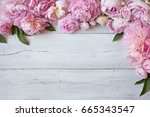 Stock photo pink peonies and roses on a wooden background 665343547