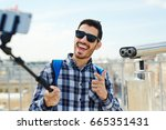 Small photo of Ecstatic adventurer making selfie while traveling