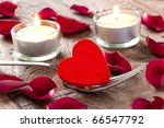 heart on fork with petals and candles - stock photo