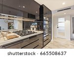 Small photo of Black pantry cupboards with a stove and kitchenware on the counter top including spoons and a mirror, the cupboards are reflective and beside the door and tile floor