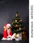 christmas tree with different gifts on black and santa girl - stock photo