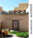 Small photo of Adobe house decorated with flower pots in the garden and on the roof top on a hot summer day