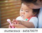 baby eating baby food   Shutterstock . vector #665670079