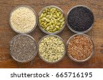 healthy seed collection (chia, hemp hearts, brown flax, pumpkin, black cumin, sesame) - top view of small glass bowls against rustic wood