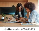 shot of two young woman working ... | Shutterstock . vector #665740459