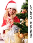cheerful santa girl stand near the gift and New-year's tree. Christmas greetings card - stock photo
