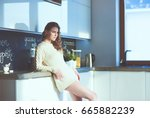 young woman standing in kitchen. | Shutterstock . vector #665882239