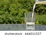 pouring milk into a glass | Shutterstock . vector #666011527