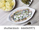 Stock photo pieces of herring with onions gherkins and boiled potatoes 666065971