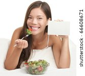 Salad copyspace. Woman eating salad showing blank sign with copy space. Healthy eating concept with young asian woman smiling looking at camera. Room for text. - stock photo