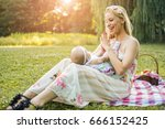 mother holding baby on lap and... | Shutterstock . vector #666152425