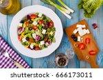 fresh greek salad on a plate.... | Shutterstock . vector #666173011