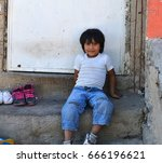 Small photo of ZAPOPAN, JALISCO, MEXICO, OCTOBER 10, 2012 MEXICAN BOY SITTING OUTSIDE OF THE FRONT Of HIS HOUSE