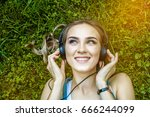 a cheerful girl listens to... | Shutterstock . vector #666244099