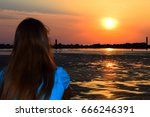 a girl looks at sunrise over... | Shutterstock . vector #666246391