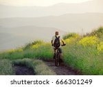 Small photo of Cyclist man riding on a country road on the hill on the background of the sunset mountains Altai mountains, Siberia, Russia