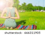 Small photo of Lissome sporty woman sitting in yoga Lotus pose with her hands behind the back
