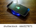 Small photo of Smartphone charging on a charging pad. Wireless charging
