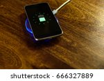smartphone charging on a... | Shutterstock . vector #666327889