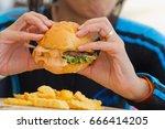 eating hamburger closeup | Shutterstock . vector #666414205