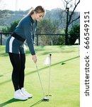 positive female golfer is ready ... | Shutterstock . vector #666549151