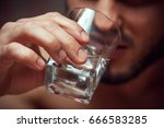 Small photo of Closeup of male adult drinking alcohol. Alcohol addiction.