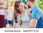 couple flirting at outdoor party | Shutterstock . vector #666597115