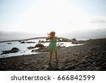 Girl Standing On Beach With...