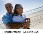 senior couple embracing on beach | Shutterstock . vector #666845365