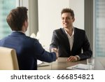 Small photo of Two cheerful businessmen shaking hands over office table, starting negotiations, hr greeting applicant arrived at job interview with handshake, good first impression, forming beneficial partnership