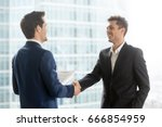 Small photo of Happy satisfied business partners shaking hands after concluding contract for services on city building background, two smiling businessmen seal good deal, binding bargain with firm strong handshake