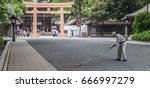 Small photo of TOKYO, JAPAN - 25TH JUNE 2017. Temple worker sweeping Meiji Jingu temple grounds. Meiji Jingu is a Shinto shrine dedicated to the deified spirits of Emperor Meiji and his spouse.