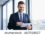 middle aged businessman using... | Shutterstock . vector #667018027