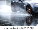 sports car driven on rainy... | Shutterstock . vector #667109605