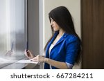 Small photo of Side view of a young woman lith long dark hair wearing a blue suit and writing on a paper standing near a window