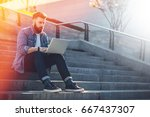 young businessman sits outdoor... | Shutterstock . vector #667437307